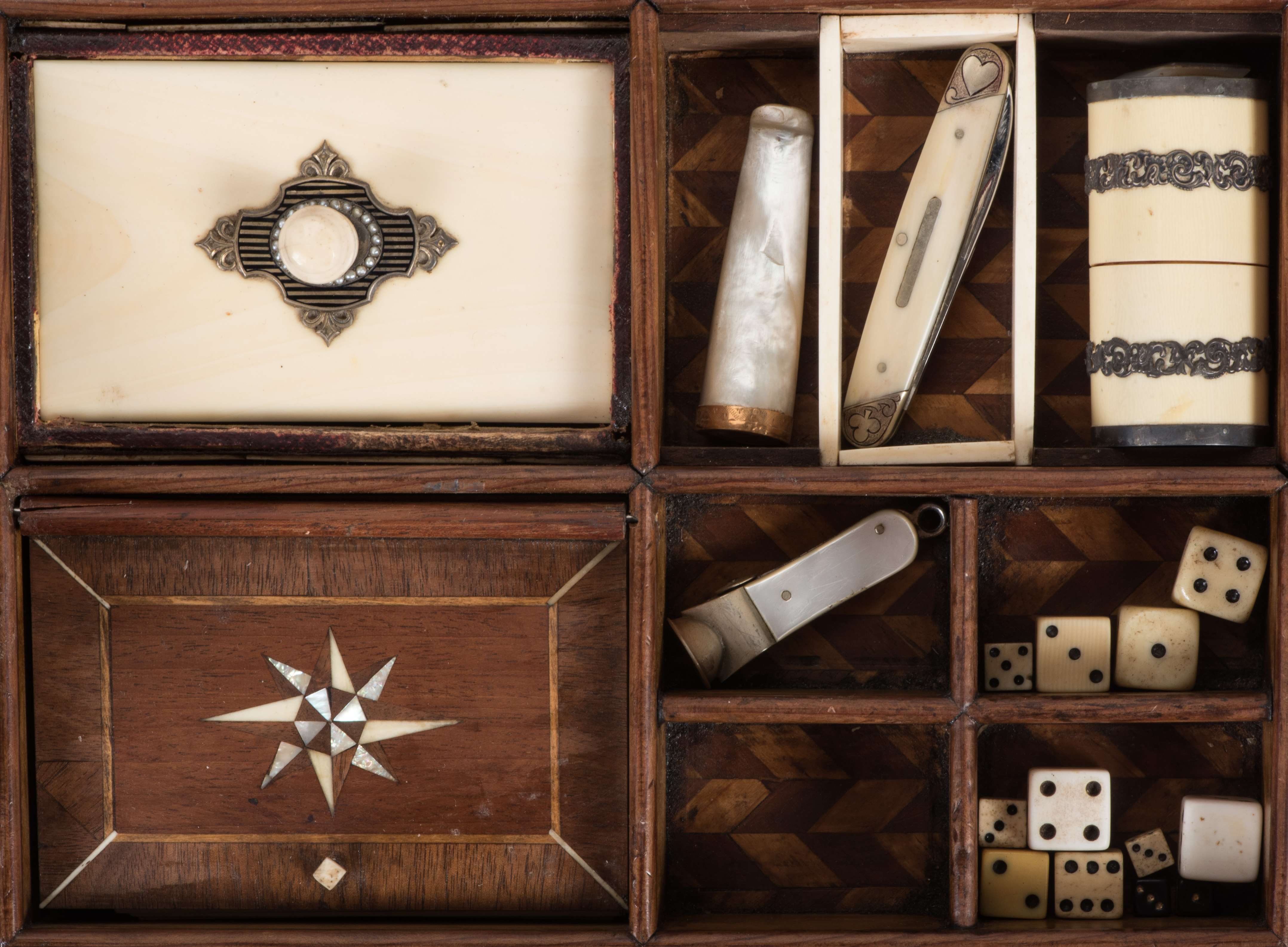 A circa 1880 American-made gambler's case, with several sets of mother-of-pearl chips, a pistol with a mother-of-pearl handle, a full set of playing cards, a cigar cutter with a mother-of-pearl handle, a two-bladed pocket knife with a scrimshawed ivory handle, an ivory dice cup, and miscellaneous dice.