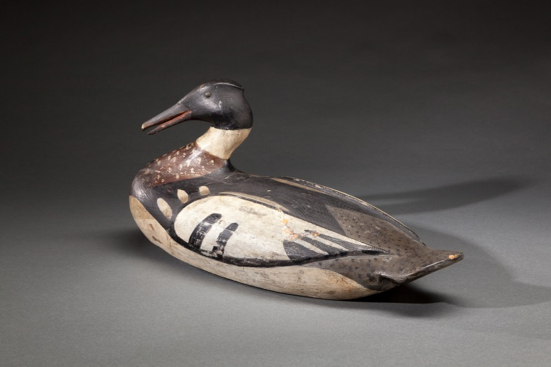 "A red-breasted merganser drake duck decoy, carved circa 1900 by Augustus ""Gus"" Wilson. It had been described as the finest Wilson decoy ever offered at auction. Copley Fine Art Auctions sold it in July 2014 for $330,000, achieving an auction record for the artist."
