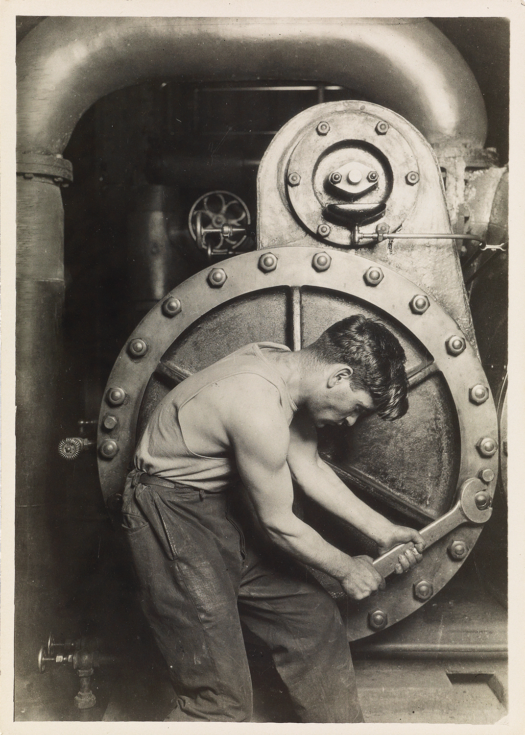 Lewis Hine's Mechanic at Steam Pump in Electric Power House, aka Power House Mechanic, a photograph printed circa 1921.