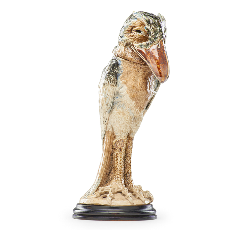 "A tall bird tobacco jar, aka a ""Wally Bird,"" by the Martin Brothers, created in London circa 1900. It is slim and compact, with a dark orange beak and a beige, cream, and grey body. It has an expression on its face that seems to say it knows you just committed a huge, embarrassing social error, and you're so ignorant that you have no idea what you just did, and why it marks you as a rube."