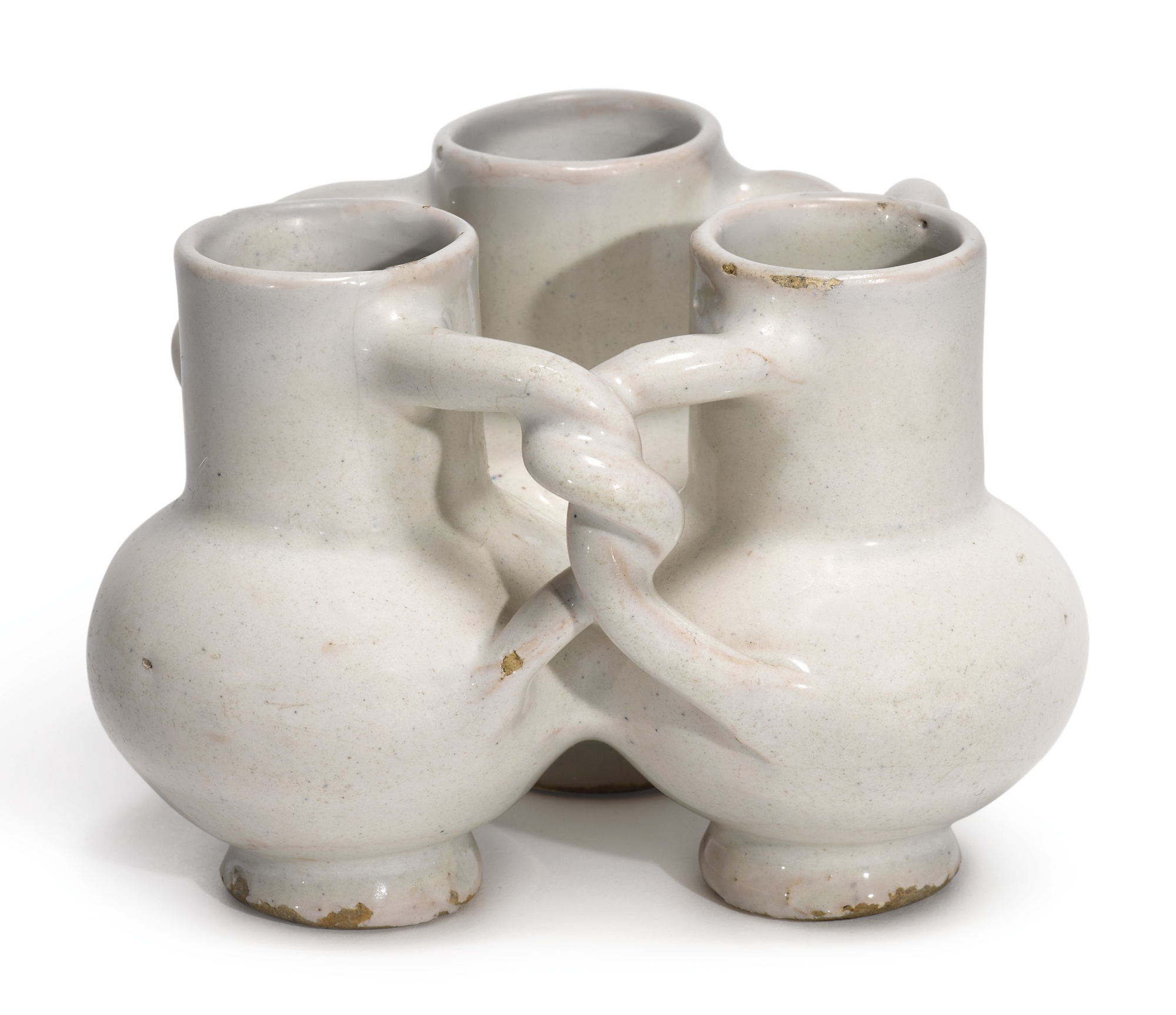 A white delftware fuddling cup made in London and dating to the mid-17th century. It looks like three jugs in one. A trio of identical vessels with bulging bodies are bound together, back to back to back, by entwined handles. The three are undecorated.