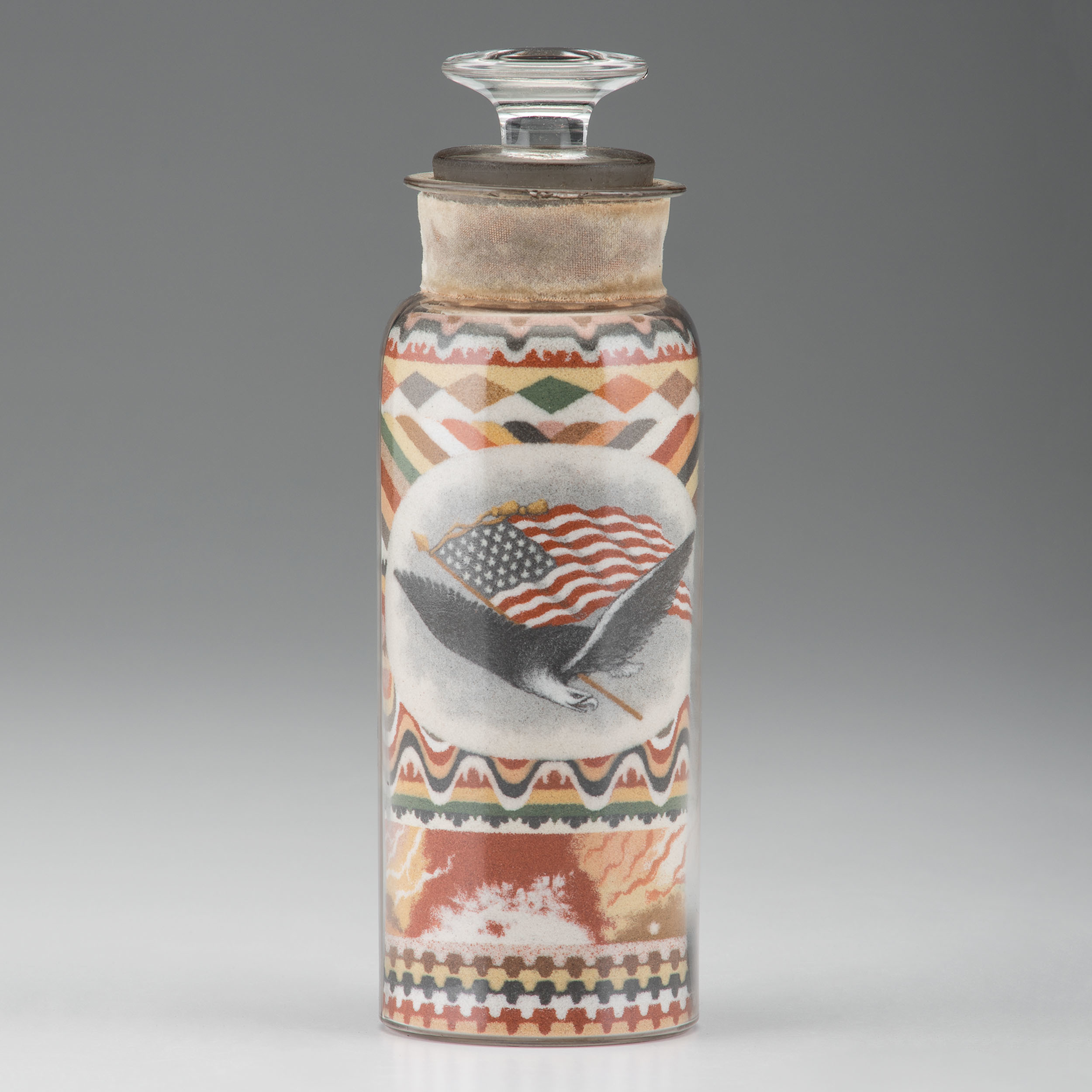 Andrew Clemens created this example of bottled sand art in 1887. It has a patriotic theme that showcases a flying eagle and a streaming American flag. Clemens developed his own techniques for arranging the layers and sections of colored sand to create elaborate, distinct imagery.