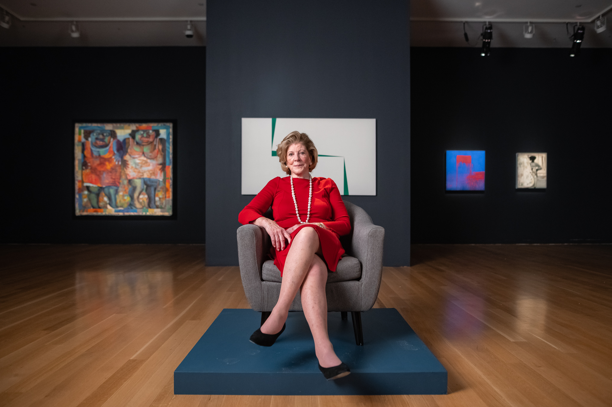Collector Agnes Gund, seated and wearing a red dress and pearls. Behind her are several selections from the 2019 By Women, For Tomorrow's Women auction at Sotheby's, including Carmen Herrera's Blanco y Verde.