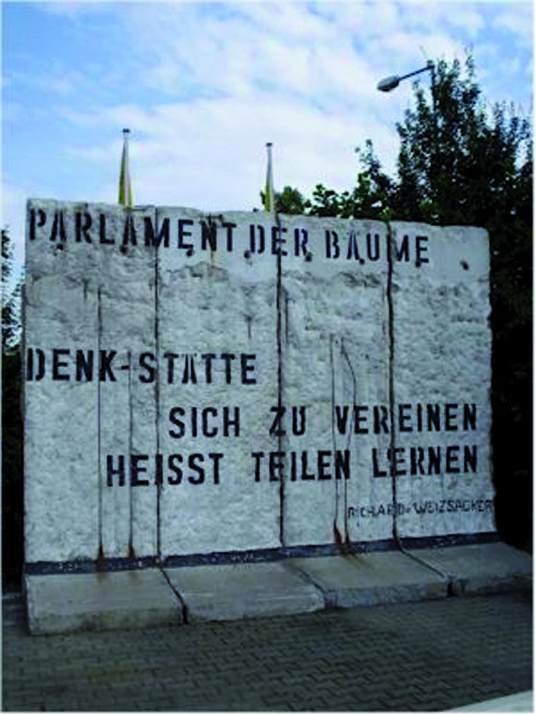 "An original four-piece segment of the Berlin Wall, standing almost 12  almost eight feet deep, and spanning more than 15 feet (including the base slabs). It once belonged to the Parliament of Trees memorial in Berlin. The German phrase stencil-graffitied on the section, spoken by then-German president Richard von Weizsäcker, translates as: ""To Unite Means to Learn to Share"". It is gray, with black lettering, and was photographed outdoors against a blue sky."