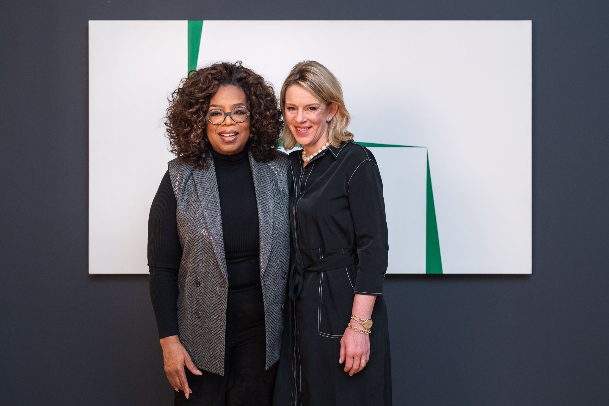 "Oprah Winfrey and Dr. Kate Windsor, head of school at Miss Porter's, standing in front of ""Blanco y Verde""."