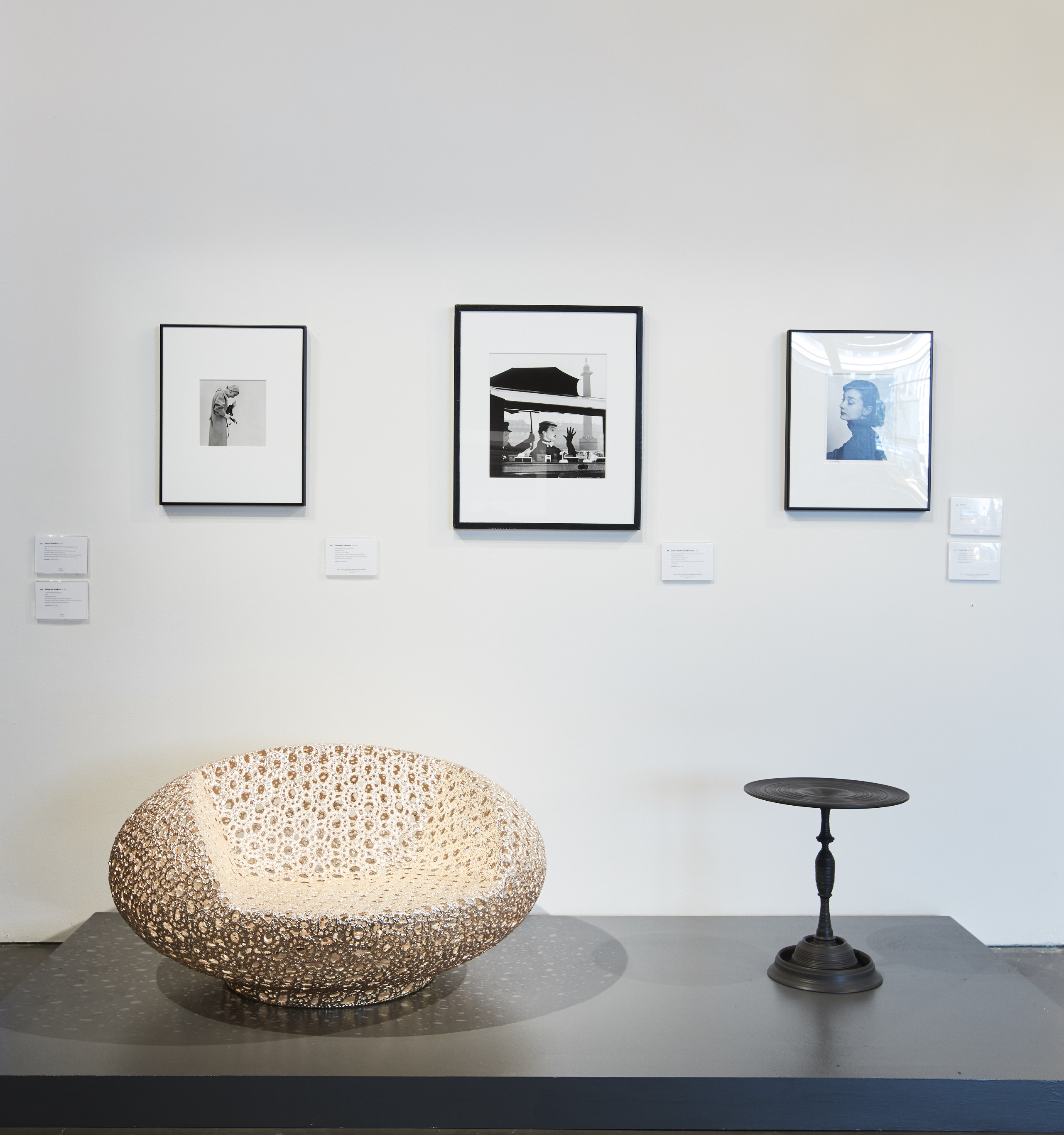 "A Marcel Wanders gold limited edition ""Bon Bon"" chair, pictured on exhibit at Phillips with a small black side table and framed photographs on the wall behind it."