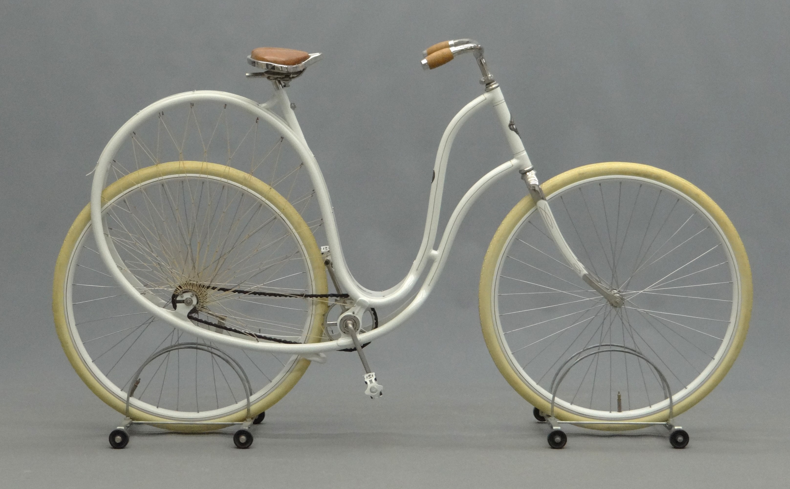 "An 1898 Cygnet ""Swan"" Ladies pneumatic safety bicycle, which has a striking looped frame painted in white."