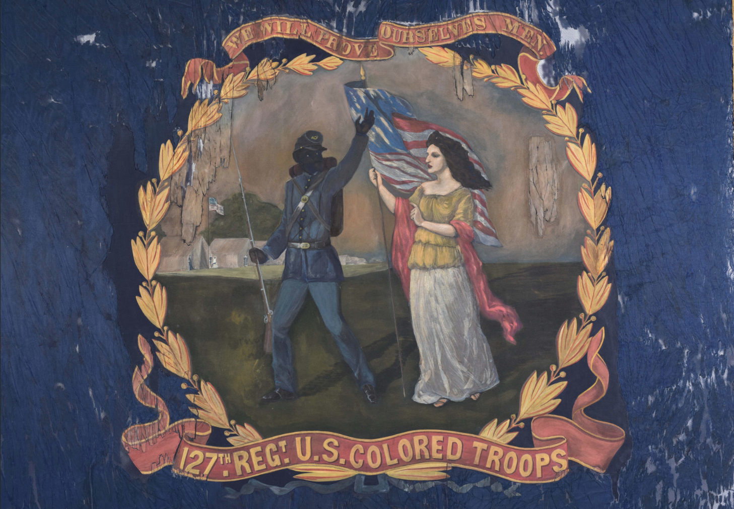 "A Civil War-era flag carried by the 127th Regiment of the United States Colored Troops and painted by African-American artist David Bustill Bowser. It shows a black Union soldier and Columbia, the female personification of America. She has pale skin and dark hair and she carries the American flag. The image is bordered by gold laurel leaves. Above it we see the motto that reads, ""We Will Prove Ourselves Men"". The blue cloth of the flag is ragged in places."