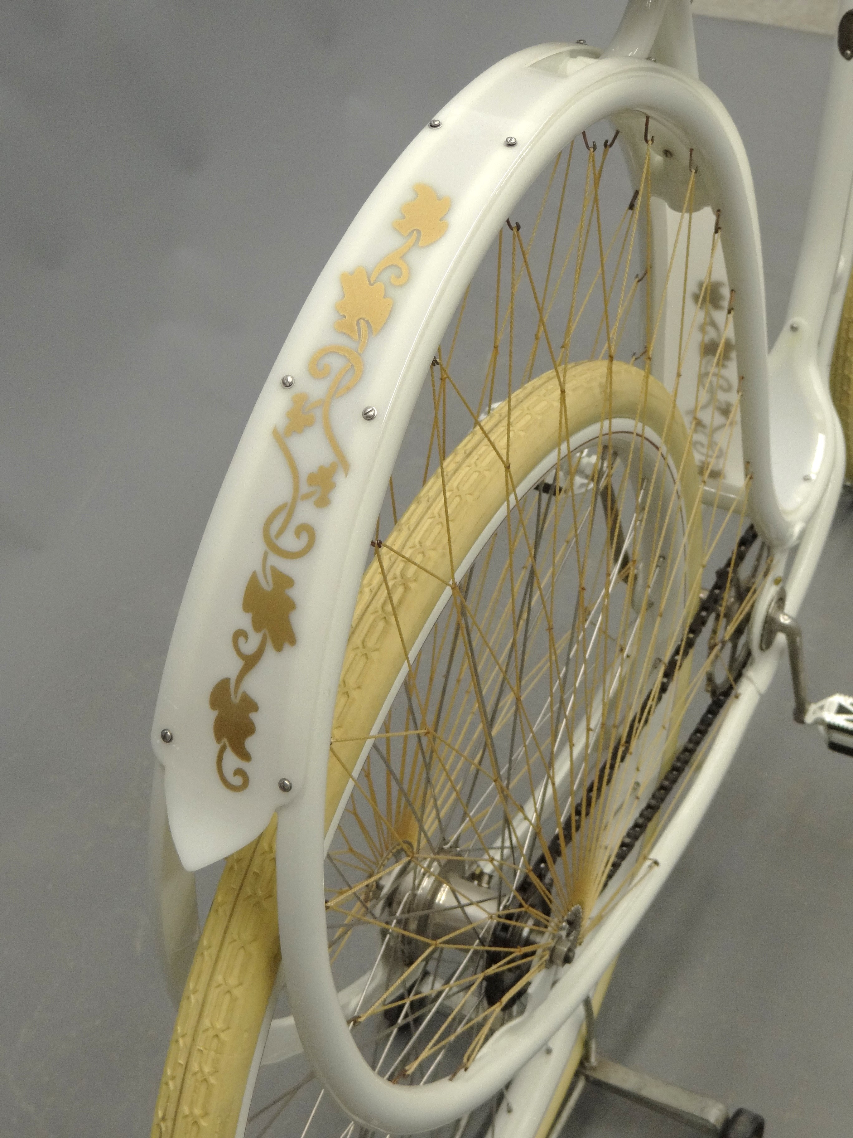"A detail shot of the back wheel of the 1898 Cygnet ""Swan"" Ladies pneumatic safety bicycle, which shows decorative gold vines painted on the back fender."