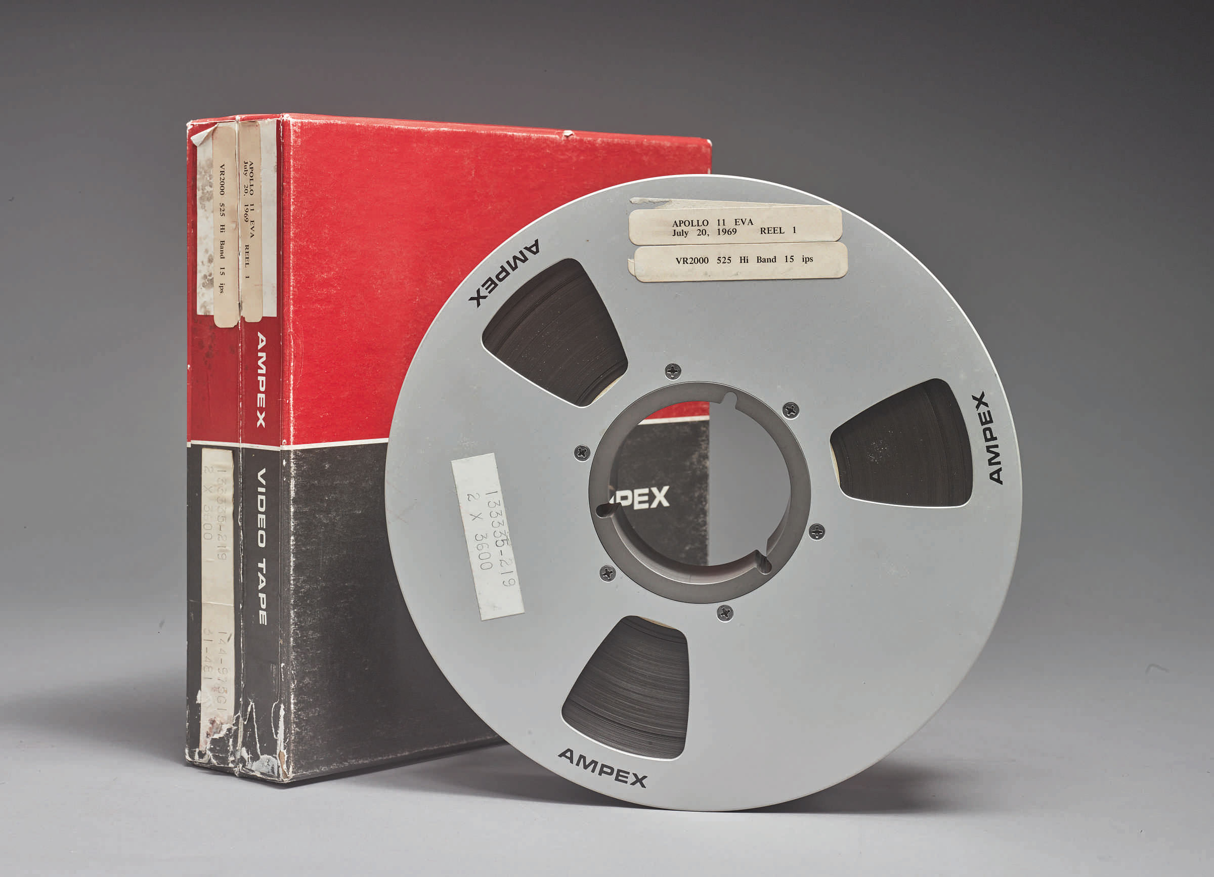 One of the three AMPEX tapes of the Apollo 11 moonwalk, shown with its red and black storage case.