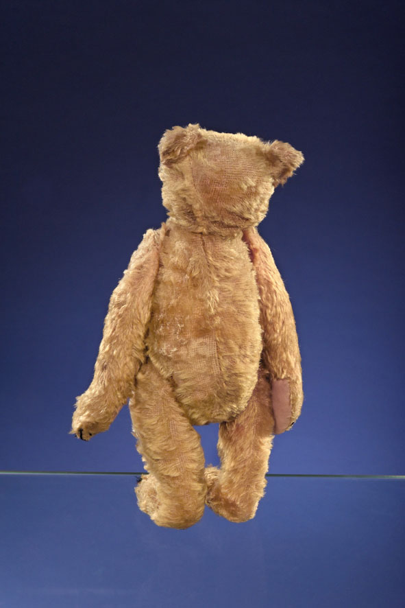 A Steiff PB28 rod bear, measuring 15 and 3/4 inches tall and created circa 1903 or 1904, shown from the rear. Thin patches are visible on the back as well as the back of the head.