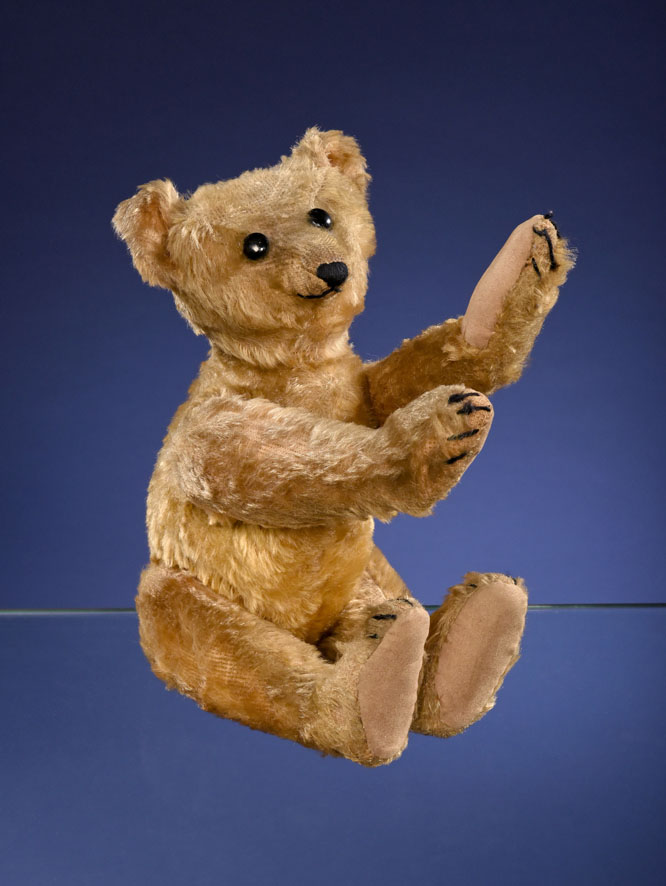 A Steiff PB28 rod bear, measuring 15 and 3/4 inches tall and created circa 1903 or 1904, shown seated.