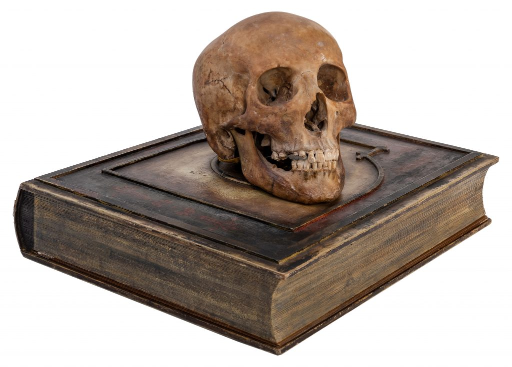 A willman talking skull automaton, created circa 1930, shown sitting on the convincing false book that houses its mechanics.