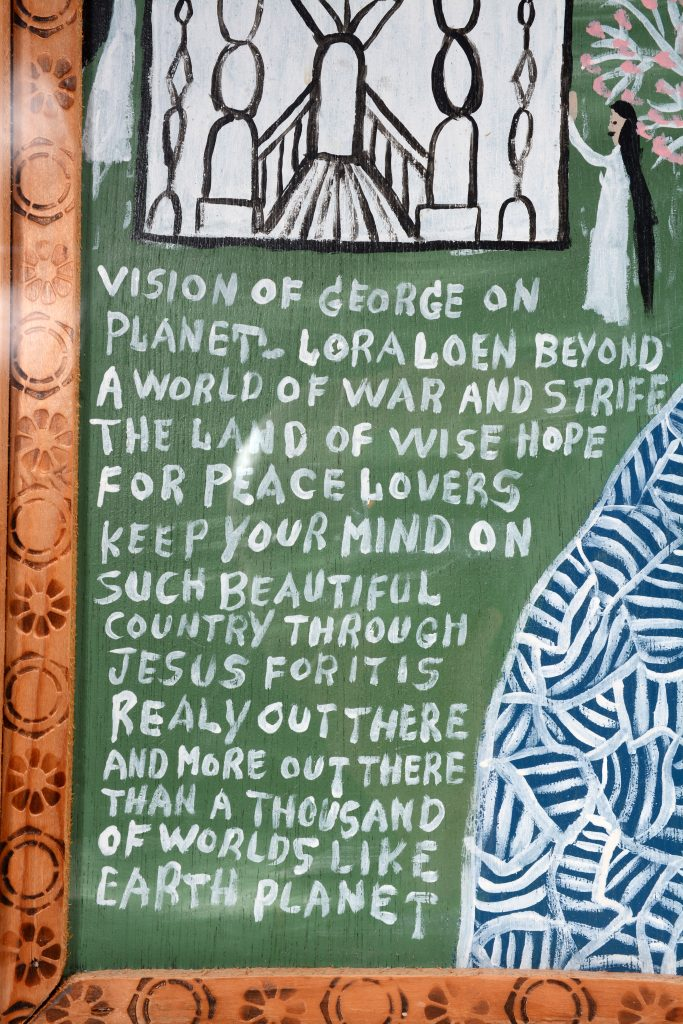 A detail of Vision of George on Planet Loraleon, a painting by the late American self-taught artist Howard Finster, which shows a handwritten message and part of a church.