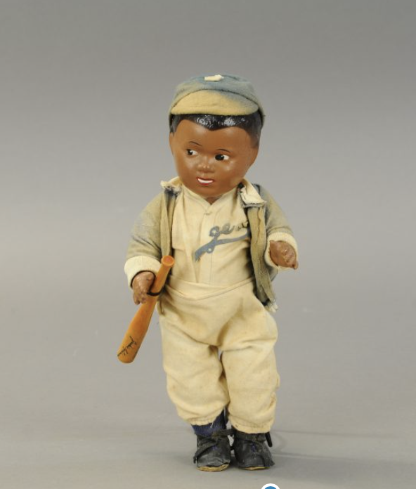The Jackie Robinson doll, shown alone, from the front, in full Dodgers uniform. Robinson's signature is visible on the toy bat.