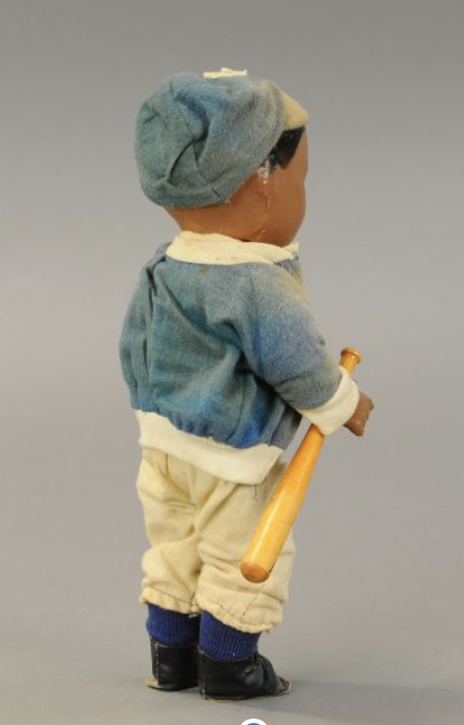 The Jackie Robinson doll, shown in full, from the rear, with the baseball bat clearly attached to the right hand.