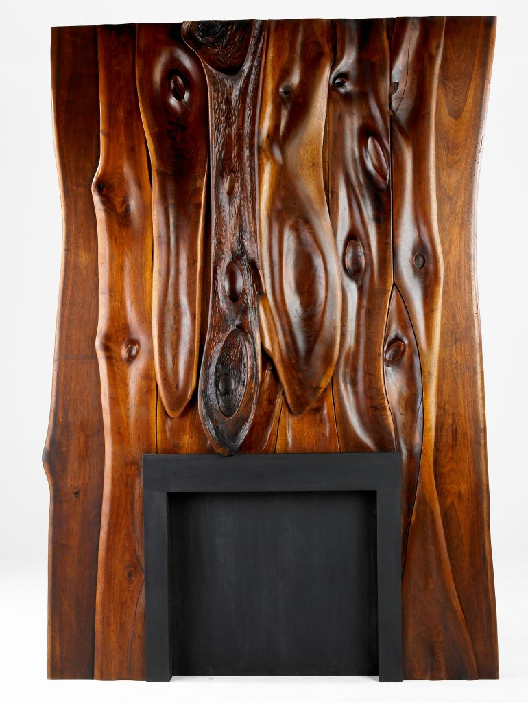 A black walnut fireplace, measuring seven and a half feet tall, created by Phillip Lloyd Powell in the mid-1950s. It set a world auction record for the artist at Rago in 2008.