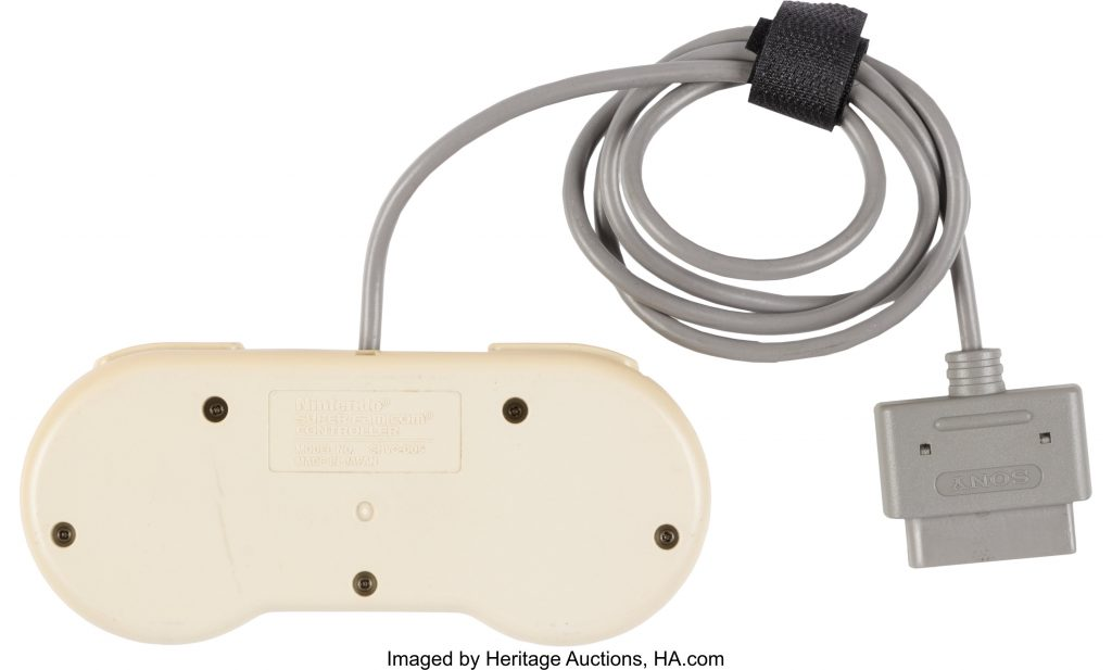 The controller for the Nintendo PlayStation prototype, shown upside down, with wiring attached. It's a little hard to see because it's beige on beige, but the information plate identifies the controller as made by Nintendo.