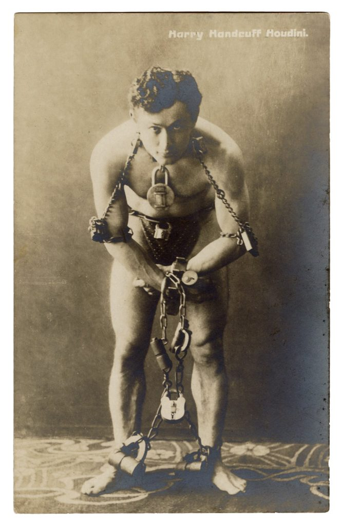 A circa 1900s postcard of Harry Houdini, elaborately bound in chains and wearing nothing but a loincloth. It bears a stamp from the Harry Houdini Collection, and it could sell for $2,500 or more at Potter & Potter.