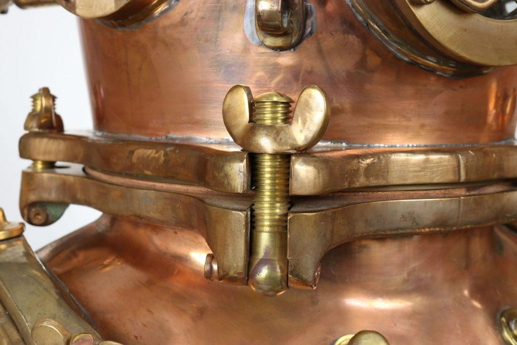 A detail shot showing two of the five bolts that secure the top, or bonnet of the Schrader diving helmet to the bottom, or neck ring.