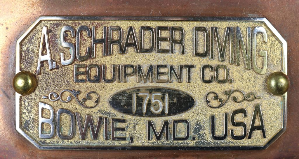 A detail shot of the name plate affixed to the front of the Schrader diving helmet.