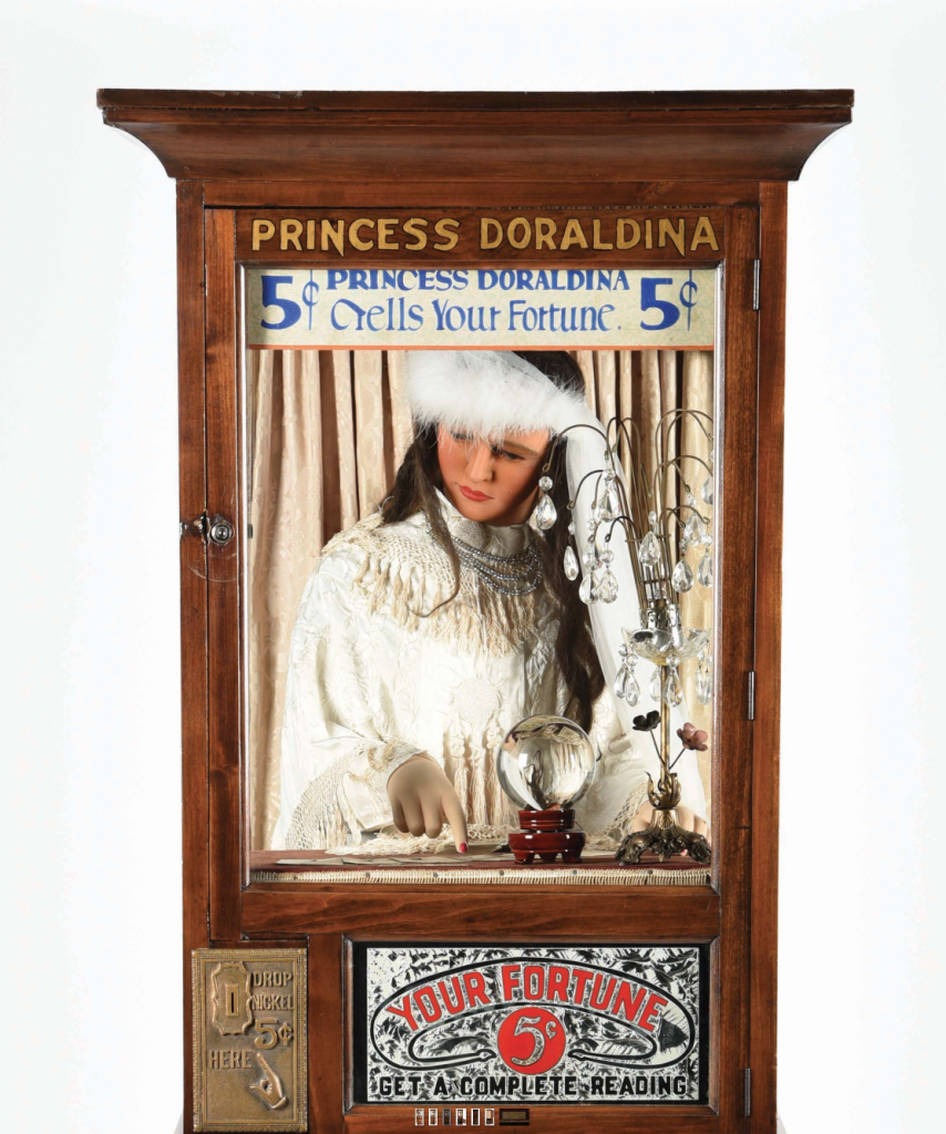 Detail shot of the restored Princess Doraldina machine, with its glass glue chip sign visible below the mannequin.