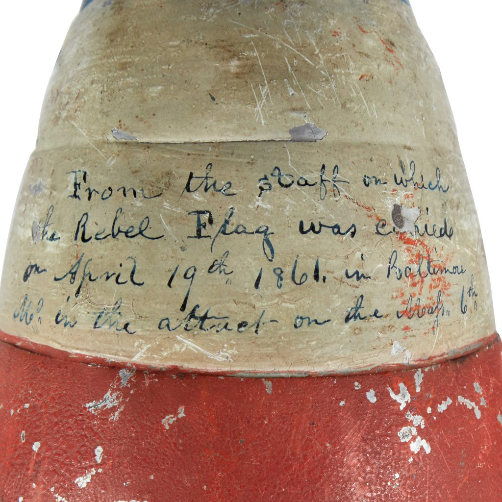 "A detail shot of the Liberty cap flag finial that displays the inked inscription, which reads: ""From the staff of which the Rebel Flag was carried on April 19th 1861 in Baltimore Md. in the attack on the Mass 6th."""