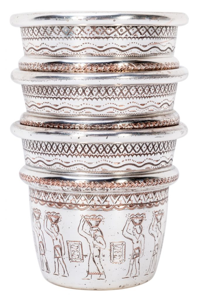 The cups in Johnny Thompson's set are silver-plated and feature engravings of Egyptian hieroglyphs. At the time they were made, a tomb in Egypt was believed to picture men performing the cups and balls routine. The hieroglyphs on Thompson's cups appear to be purely decorative and do not replicate the famous, since-debunked ones in the scene in the tomb.