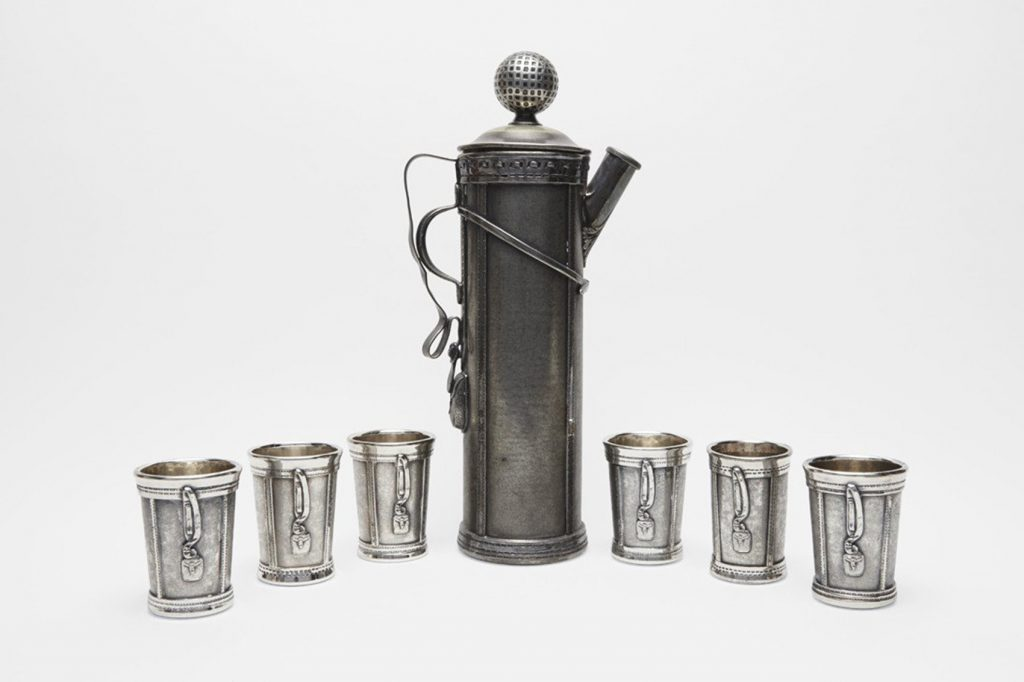 A silver-plated golf-themed cocktail set, created circa 1926 and regarded as the first figurative cocktail set. It is not complete, however. The full set consists of a shaker, six cups, and a tray.