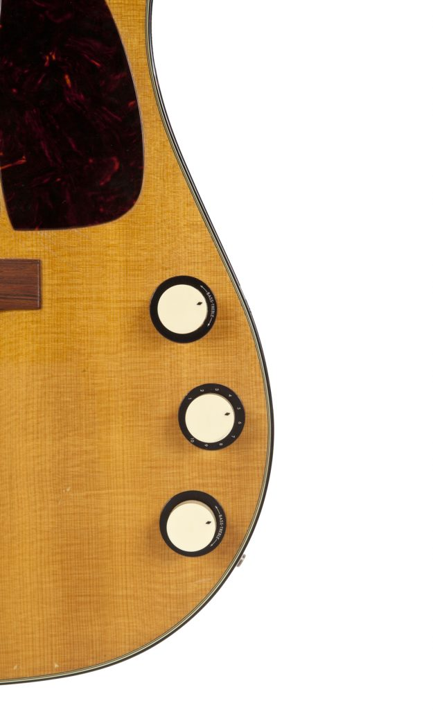 A detail shot of the vintage Martin owned by Kurt Cobain, showing three knobs on its right side.