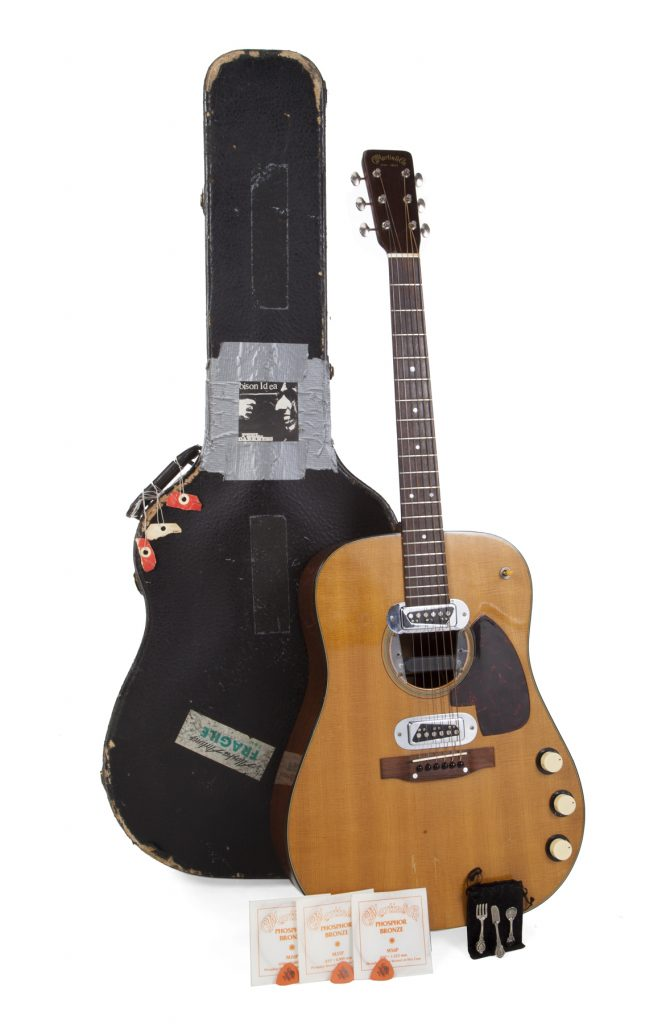 The vintage Martin guitar owned by the late Kurt Cobain, shown in full, with its hard case, and items found inside the case.