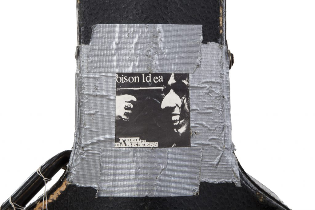 A closeup on a Poison Idea flyer that Kurt Cobain duct-taped to the neck of his guitar case. It touts the punk band's 1990 album Feel the Darkness.