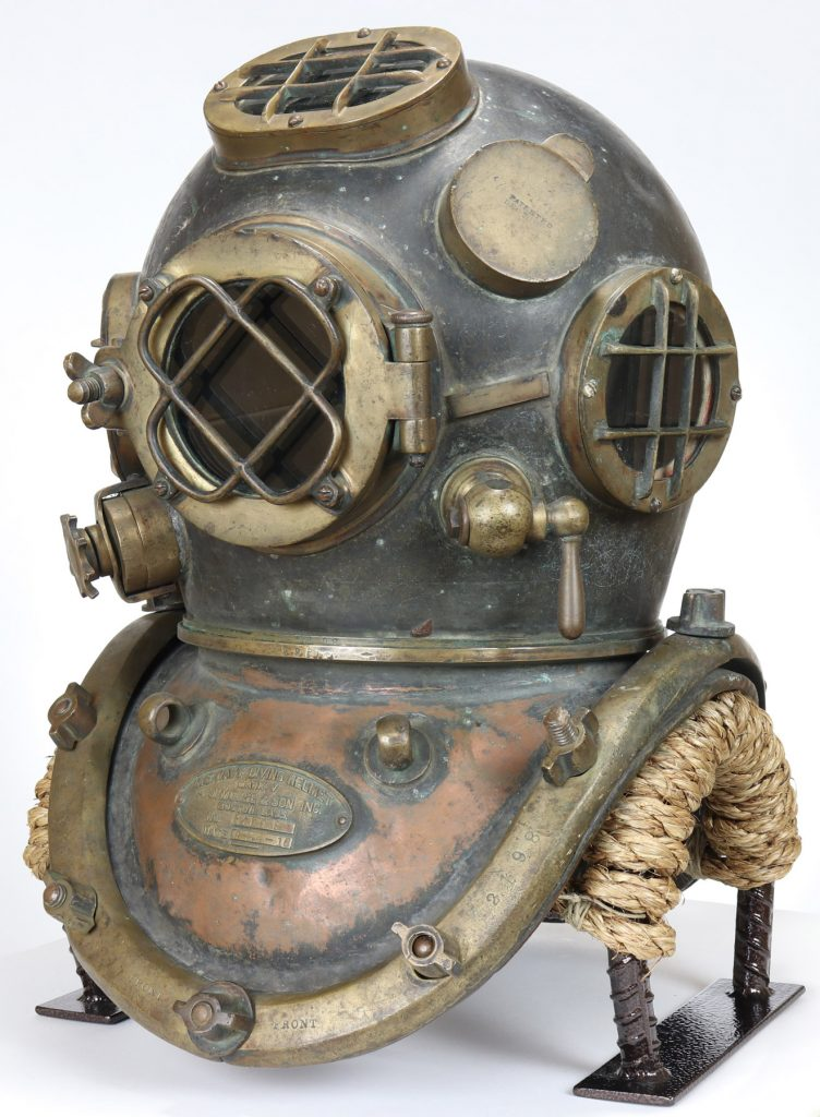 A front three-quarters view of the diving helmet, clearly showing the speaker fitting at the left temple and the spitcock valve on the left side of the jaw.