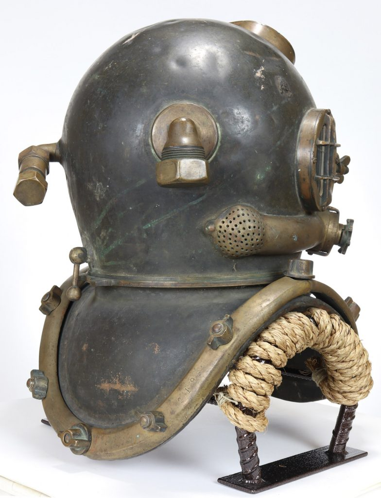 A rear three-quarters view of the diving helmet. The ports for the air line and the communications line are visible.
