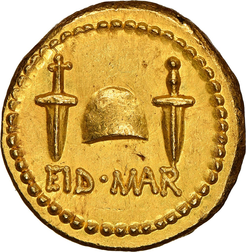 "The reverse of the gold Eid Mar coin shows a pair of daggers, representing the murder weapon and the two men who conceived the coup, Brutus and Cassius. The hat in the middle was of a style issued to newly freed Roman slaves. ""Eid Mar"" is a truncated phrasing for the Ides of March, the date of the assassination."