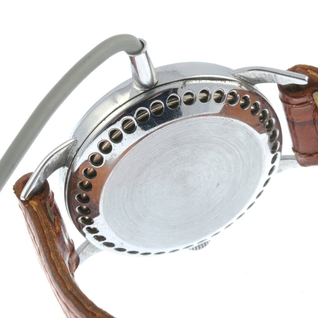If you failed to spot the fact that the watch's hands never move, the perforations on the back of the case would give it away. No real watch needs these--they exist to help the concealed microphone pick up sound.
