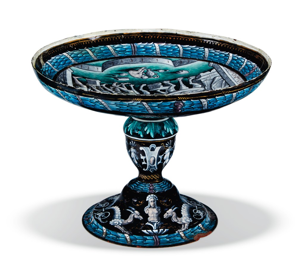 "So-called ""grotesques"" and other amusing figures decorate the stem of the Limoges enamel tazza."