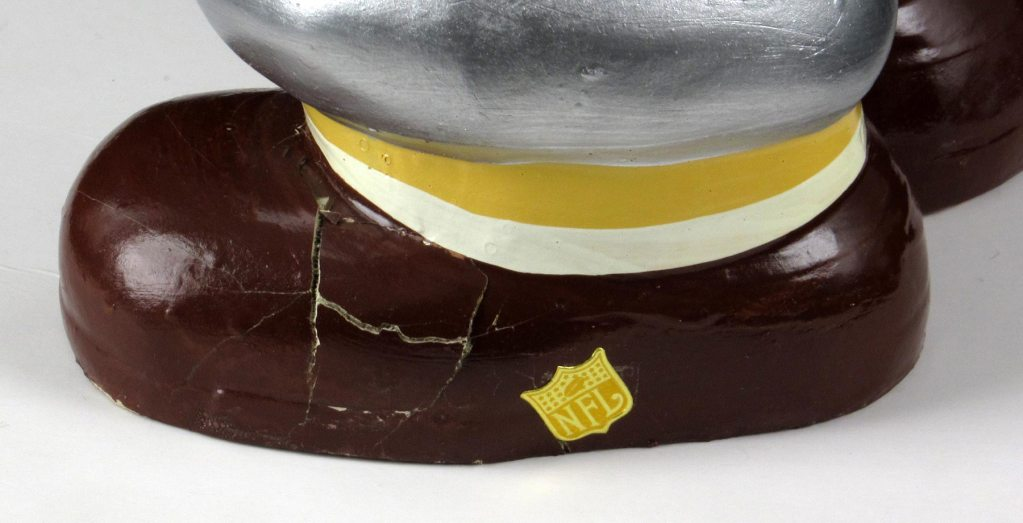 A detail shot of the left foot of the jumbo NFL bobblehead, which clearly shows the NFL logo. Because a Japanese company made the toy in the early 1960s, well before the first Super Bowl, the league probably wasn't approached for permission.