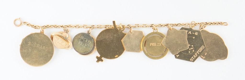 Jo Schirra's charm bracelet shown in reverse. The jewelry features nine space-flown charms.